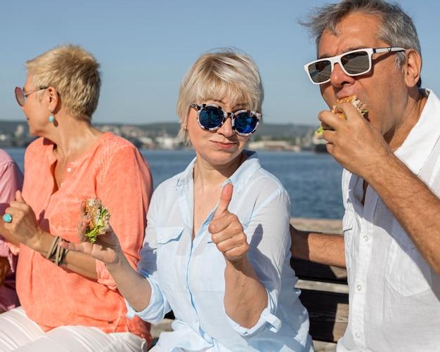 Пара ест гамбургер на открытом воздухе и показывает палец вверх