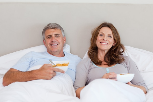 Couple eating cereals in bed