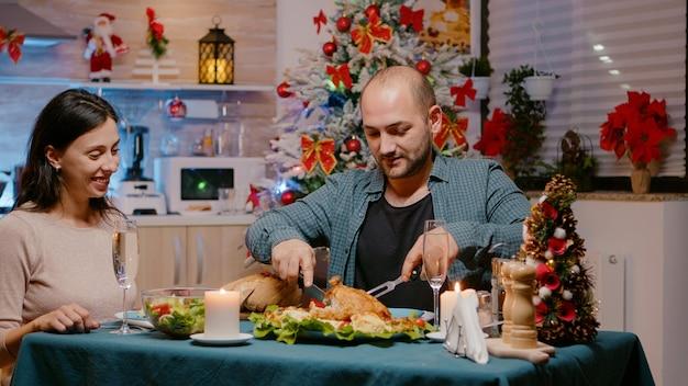 クリスマスイブのお祝いディナーで鶏肉を食べるカップル