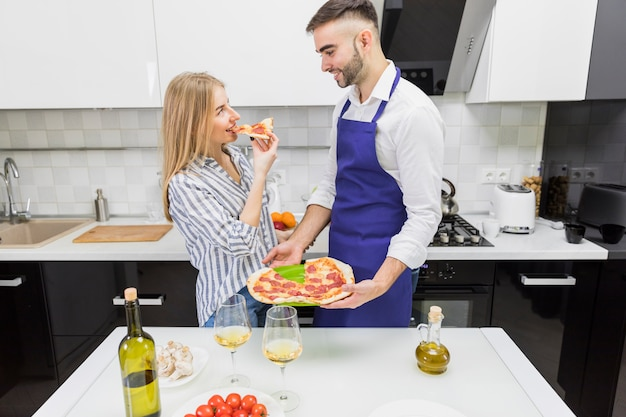 Couple eating cooked pizza in kitchen