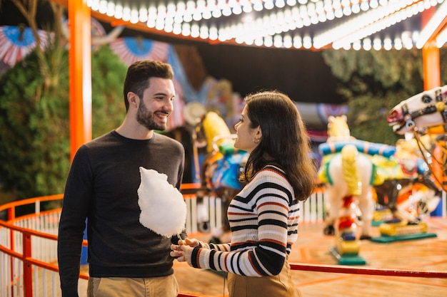 Couple eating cotton candy in a theme park