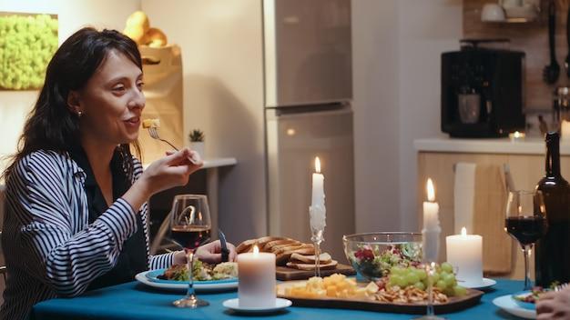 Coppia mangiare e bere vino con la donna in primo piano durante la cena festiva in cucina. parlare felicemente seduti al tavolo della sala da pranzo, godersi il pasto a casa con momenti romantici a lume di candela