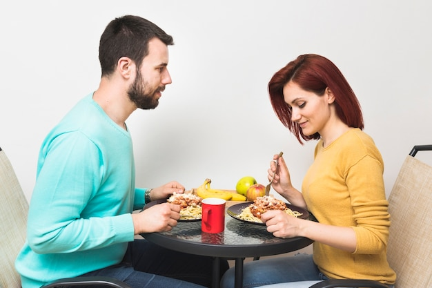 Couple eating food at home