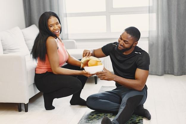 Пара ест фрукты после тренировки дома