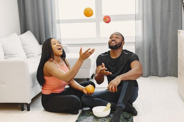 自宅でトレーニング後に果物を食べるカップル