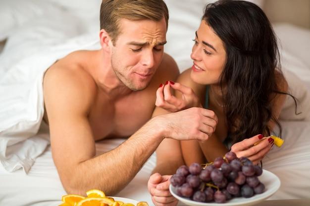ベッドで果物を食べるカップル。