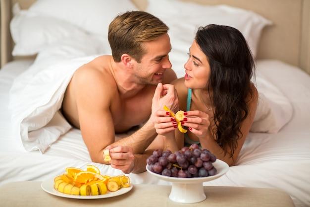 寝室で果物を食べるカップル。