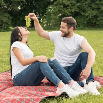 Couple eating grapes con a picnic blanket