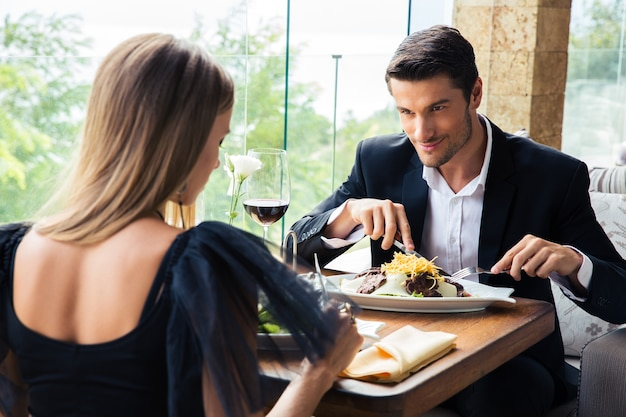 レストランで赤ワインを飲みながら食事をするカップル