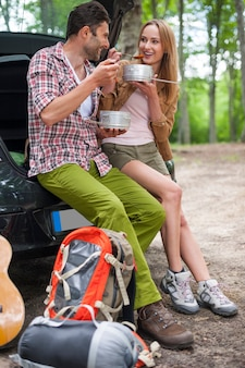 하이킹을 가기 전에 차에서 먹는 커플