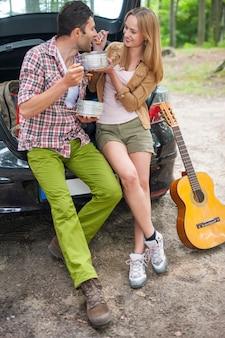 ハイキングに行く前に車で食べるカップル