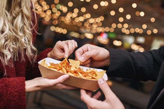 Пара ест мексиканские тортильи. блюдо мексиканской кухни начос кон карне. концепция мексиканской кухни. вид сверху, деревянный фон