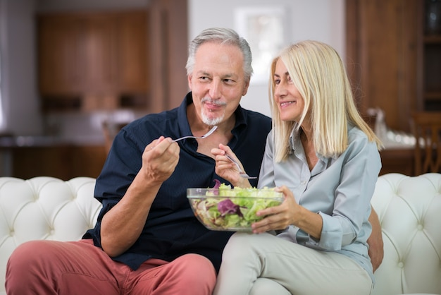 Couple eating a mixed salad in their apartment