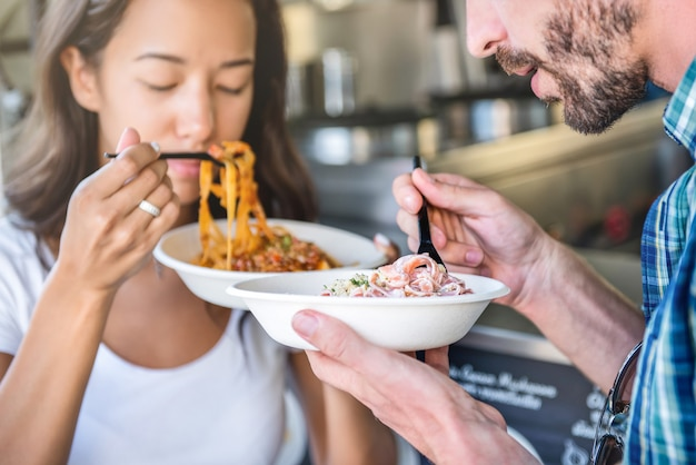 Couple eating pasta from food truck with pleasure