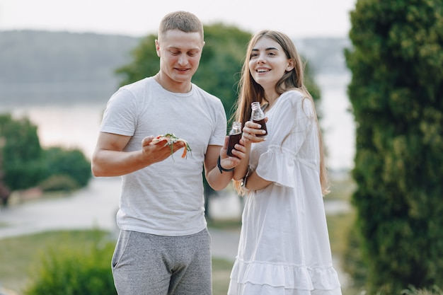 Пара ест пиццу и пьет в природе