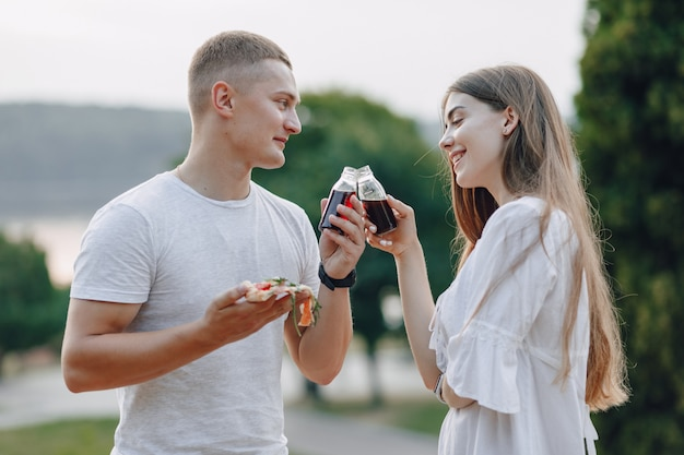 Couple eating pizza and drinking in nature