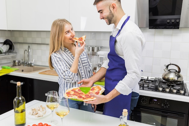Couple eating pizza in kitchen