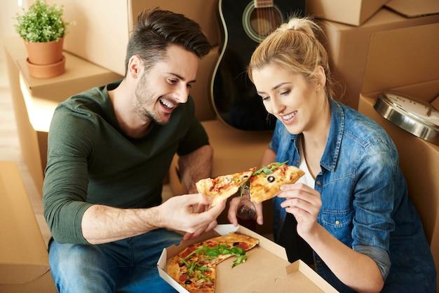 Coppia che mangia pizza accanto a scatole per trasloco
