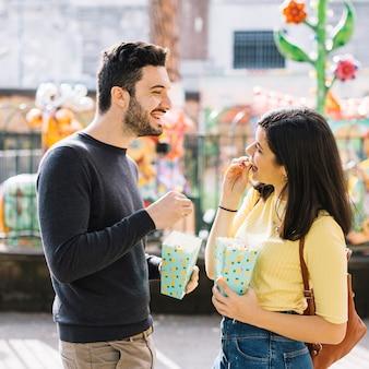 テーマパークでポップコーンを食べるカップル