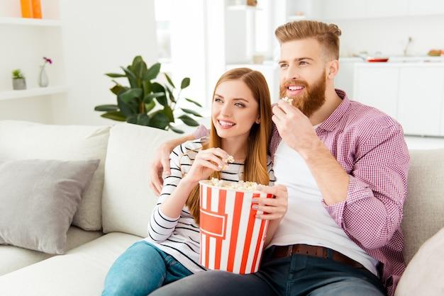 집에서 소파에 팝콘을 먹고 tv를 보는 커플