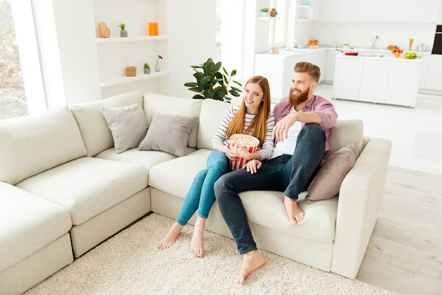 Пара ест попкорн на диване дома и смотрит телевизор
