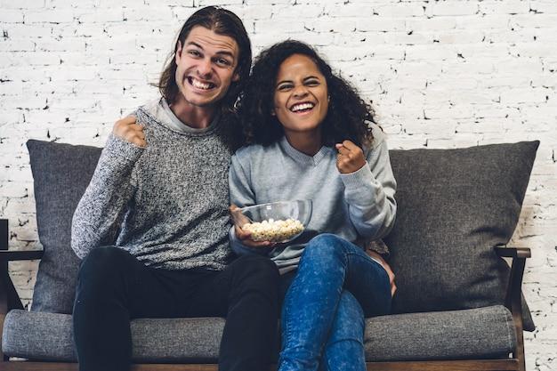 カップルが一緒にポップコーンを食べて、家のソファーでテレビを見ています。友情とパーティーのコンセプト