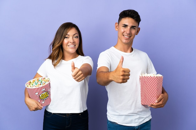 Couple eating popcorn while watching a movie on purple giving a thumbs up gesture because something good has happened