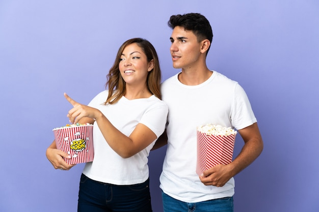 Couple eating popcorn while watching a movie on purple presenting an idea while looking smiling towards