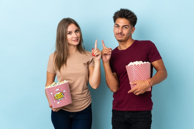 Couple eating popcorn while watching a movie on purple showing and lifting a finger in sign of the best