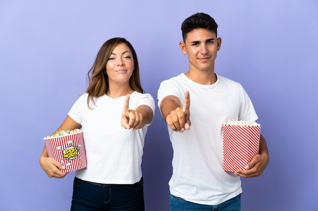 Couple eating popcorn while watching a movie on purple showing and lifting a finger