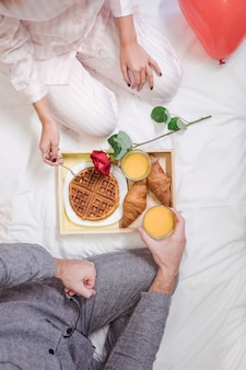 Couple eating romantic breakfast on white bed
