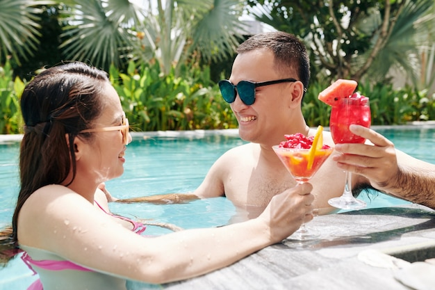 Couple eating smoothie in swimming pool