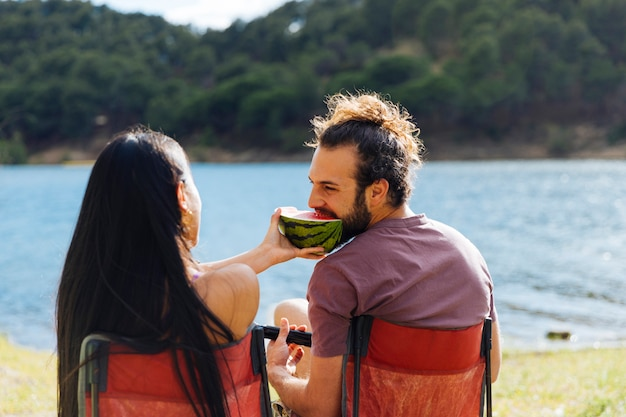 Couple eating watermelon on river shore