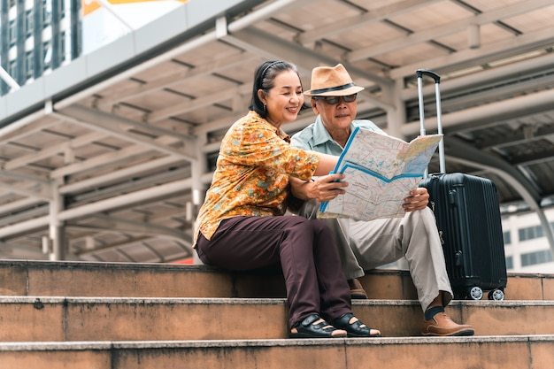 Couple of elderly asian tourists visiting the capital happily and having fun and looking at the map to find places to visit.