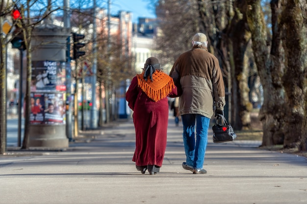 A couple of eldery people in hands are walking through the city street.