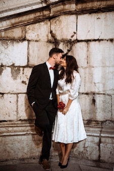 Couple in elegant clothes kissing in street