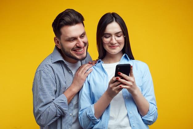Пара обнимает друг друга и радостно смотрит на мобильный телефон