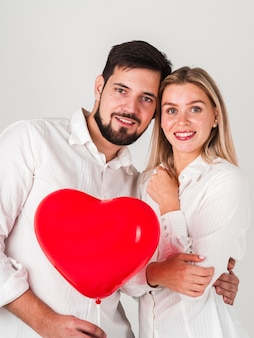 Couple embraced holding valentines balloon