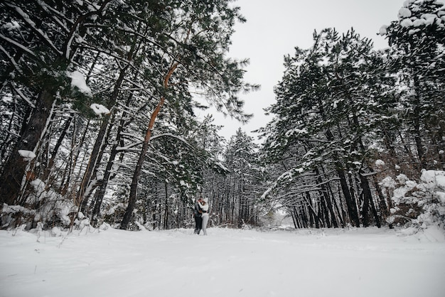 A couple embraces in a snowy forest
