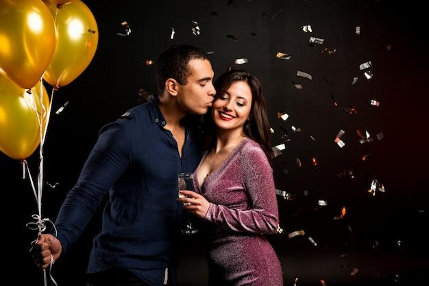 Пара обнимается на новогодней вечеринке