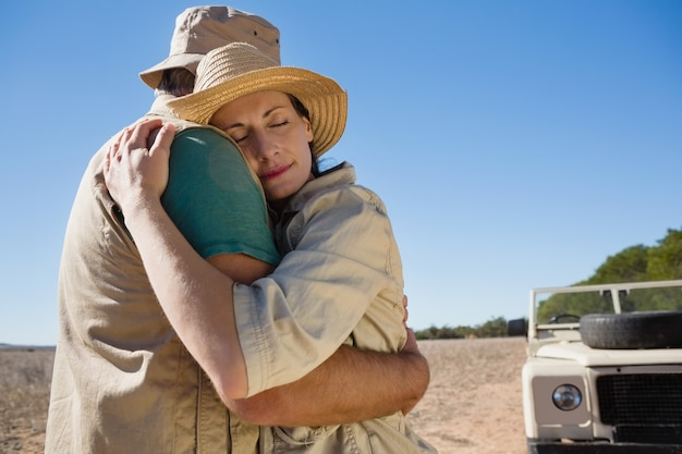 Couple embracing by off road vehicle on field