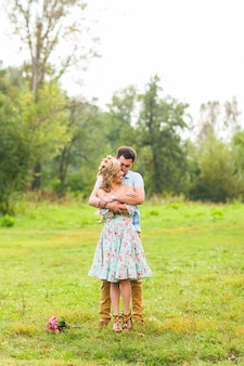 Couple embracing on the countryside. young romantic man and woman standing and hugging each other with tenderness on nature.