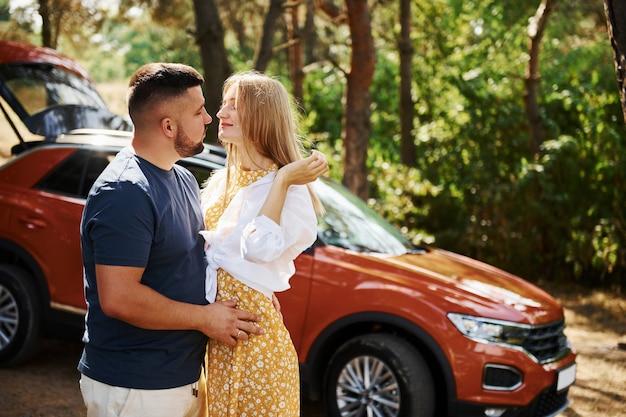 Пара, обнимая друг друга в лесу перед современной машиной.