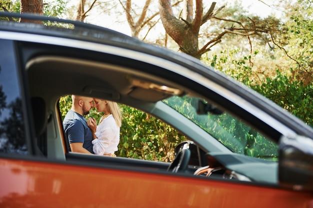Пара, обнимая друг друга в лесу возле современного автомобиля.