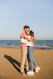 Couple embracing each other kissing near seashore at beach