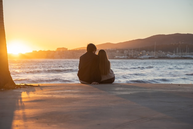 A couple embracing each other with a beautiful sunset in the background by the sea