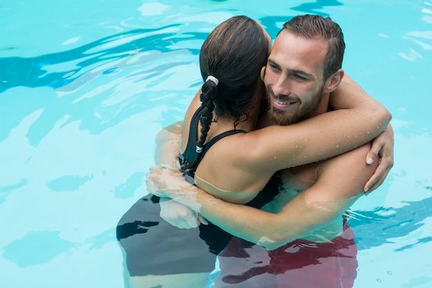 Пара, обнимающаяся в бассейне