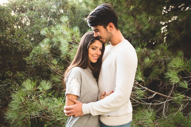 Couple embracing and the man kisses the woman in the hair Free Photo