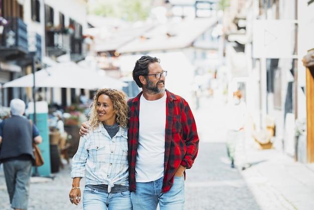 街の通りを歩きながら抱きしめるカップル。通りを歩き回っている間楽しんでいる幸せなカップル。街のストリートシーンを眺めながら一緒に歩いているカップル