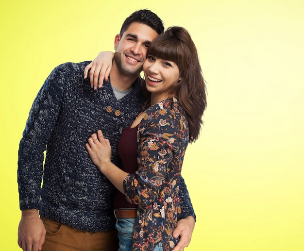 Couple embracing with a yellow background